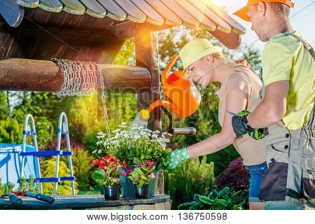Married Young Couple Working in Their Backyard Garden. Woman Watering Flowers and Her Husband Preparing For Plants Trimming. Couples Taking Care of Backyard Garden. Garden Hobby.