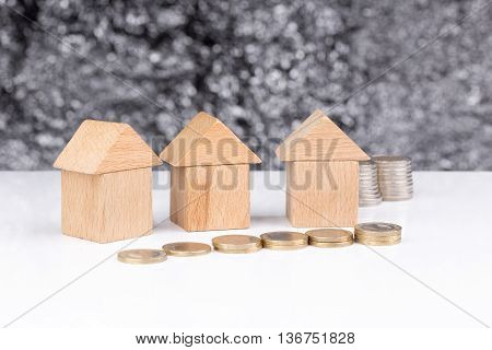 Three houses made of wooden blocks with a blurry background and coins