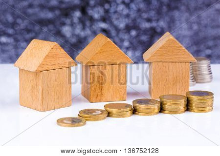 Wooden block houses and coin stacks in a row