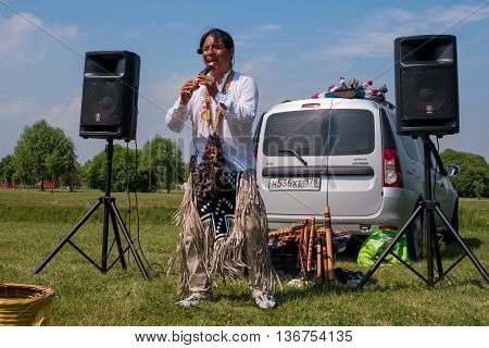 Saint-Petersburg Russia - June 26 2016: Busker dressed as an Indian playing the flute. He plays Latin music.