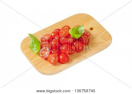Halved cherry tomatoes on cutting board