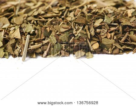 Surface covered with dry mate tea leaves as a copyspace background composition