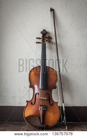 Classical violin and bow on wall background