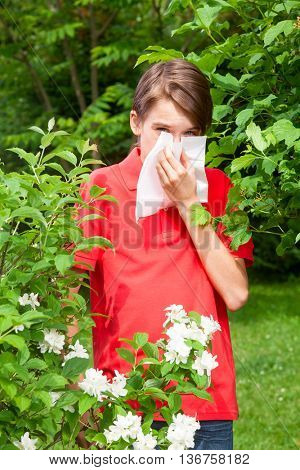 Teen boy with hay fever blowing his nose allergic to bloom flowers in a spring garden