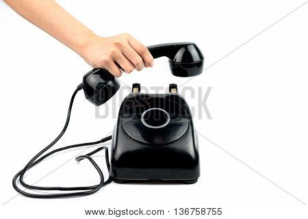 Hand picking up black vintage phone with no dial on white background.