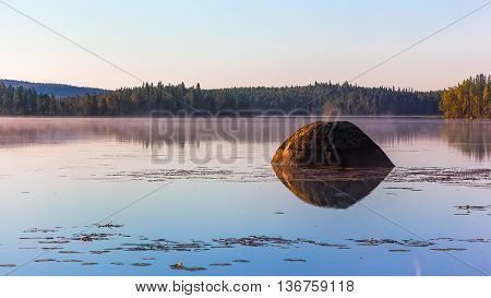 Huge boulder with a reflection in the water of the northern misty lake surrounded by evergreen forest at dawn.