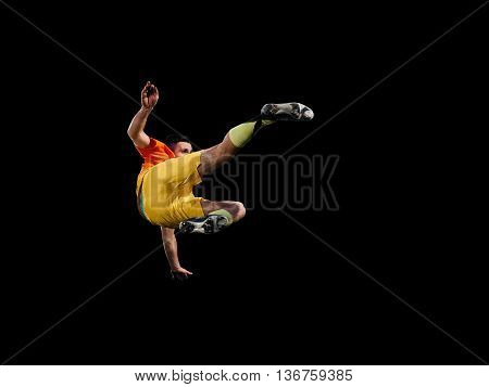 Caucasian soccer player in blue uniform kicking on training black background