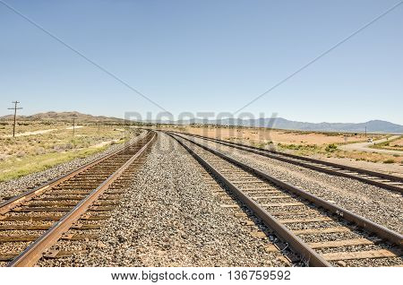 Three sets of railroad tracks curving away from the mountains in rural Utah