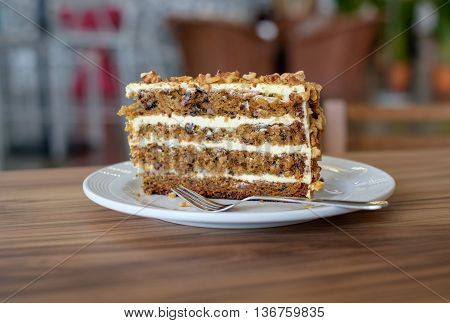Sliced of carrot cake on white plate on wooden table in cafe.