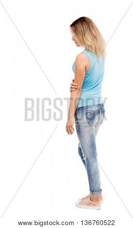 back view of standing young beautiful  woman.  girl  atching. Rear view people collection.  backside view of person. I. The girl in jeans and a blue t-shirt is thoughtfully head bowed down.