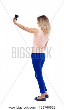 back view of standing young beautiful  woman  and using a mobile phone. girl  watching. Rear view people collection.  backside view of person.  Blonde in blue pants makes self on a compact camera.