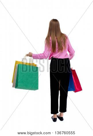 back view of woman with shopping bags . beautiful brunette girl in motion.  backside view of person.  Isolated over white background. Woman in pink holding at arm's length with shopping bags.