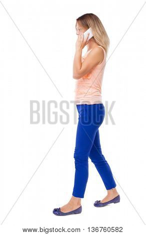 side view of a woman walking with a mobile phone. back view ofgirl in motion.  backside view of person. Isolated over white background. Blonde in blue pants right away speaking on the white smartphone