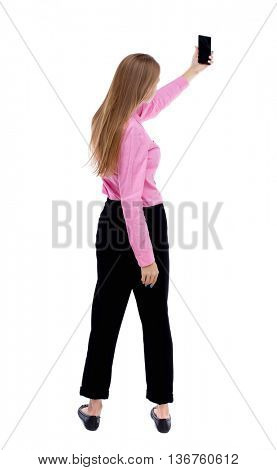 back view of standing young beautiful  woman  and using a mobile phone.  Rear view people collection.  backside view of person.  Isolated over white background. Turning left takes smartphone girl self