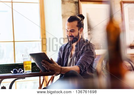 people and technology concept - happy man with tablet pc computer drinking beer at bar or pub