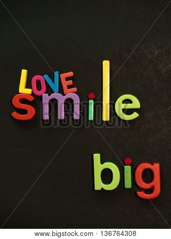 Love and smile.. BIG! Inspirational message in vibrant colorful magnet letters on black background