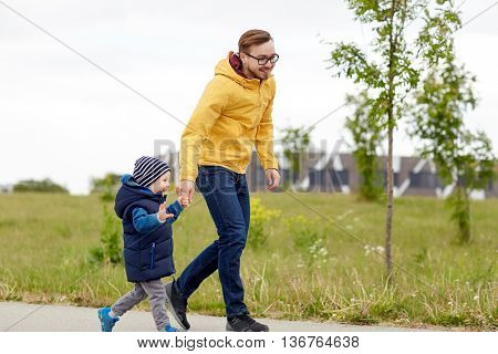 family, childhood, fatherhood, leisure and people concept - happy father and little son walking outdoors