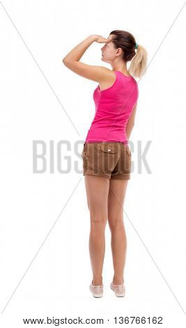back view of standing young beautiful  woman.  girl  watching. Rear people collection.  backside of person.  Isolated over white background. Blonde in brown shorts is shielding her eyes from the sun.