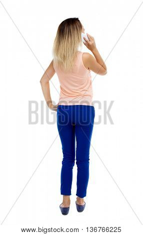 back view of a woman talking on the phone.  backside of person.  Rear people collection. Isolated over white background. Blonde in blue trousers pressed to his ear listening to the phone.