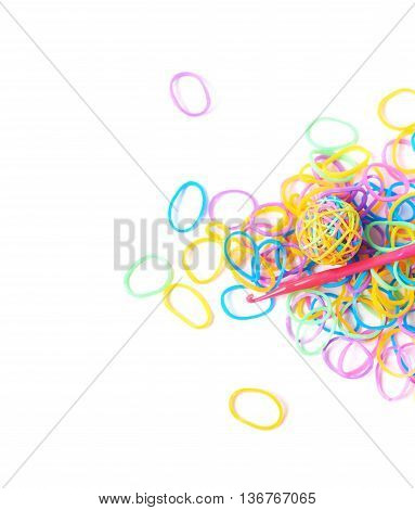 Pile of multiple colorful rubber toy loom bands isolated over the white background, close-up crop fragment foreshortening
