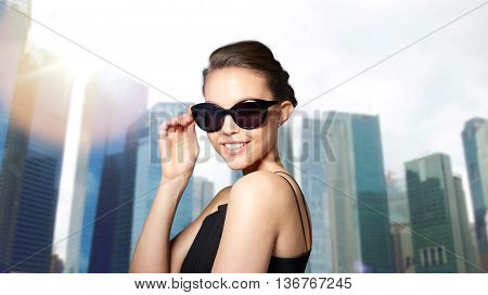 accessories, eyewear, fashion, people and luxury concept - beautiful young woman in elegant black sunglasses over city skyscrapers background