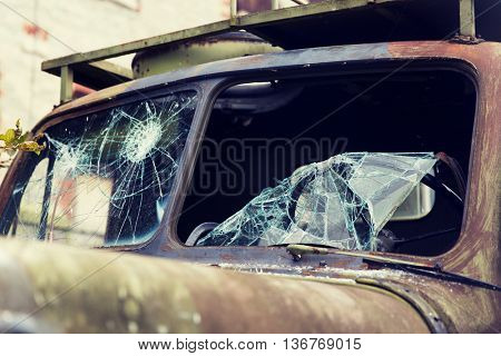 wartime, damage and danger concept - war truck with broken windshield glass outdoors