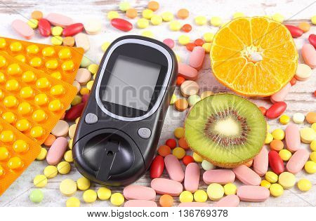 Glucometer for measurement sugar level fresh fruits and medical pills tablets or supplements diabetes healthy lifestyle and nutrition