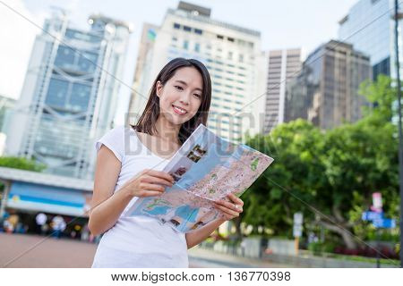 Woman looking for location on city map in Hong Kong