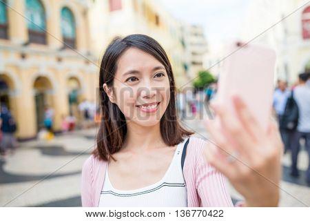 Woman using mobile phone to take selfie in Senado Square of Macau city