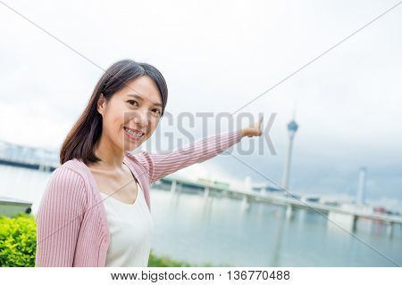 Woman finger pointing to the Macau tower