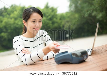 Woman pay by credit card on pos terminal with NFC