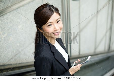 Businesswoman holding cellphone and standing on escalator