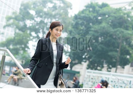 Businesswoman walking down the step