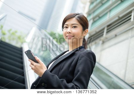 Young businesswoman hold with mobile phone and standing at escalator