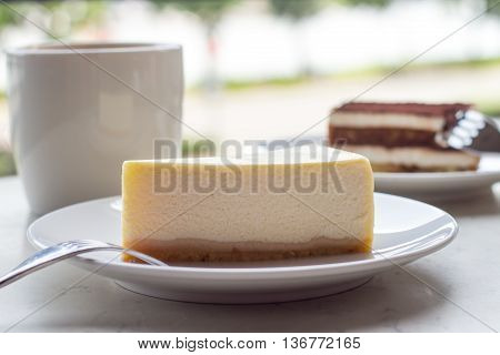 Cheesecake. Slice of Plain New York Cheesecake on white plate. Cup of art cappuccino coffee.