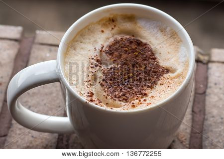 Cup of art cappuccino coffee. A cup of coffee with heart pattern in a white