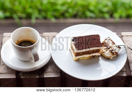 Cup of coffee on table in cafe. Tiramisu Cake.