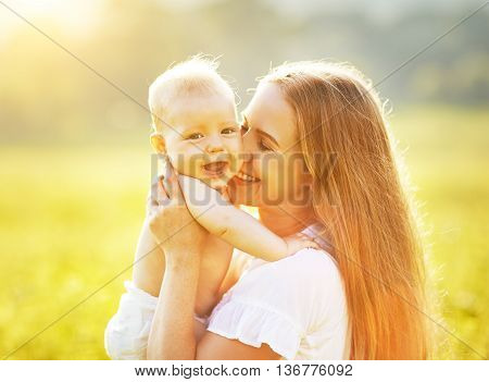 happy family mother and baby hugging and kiss in summer on the nature