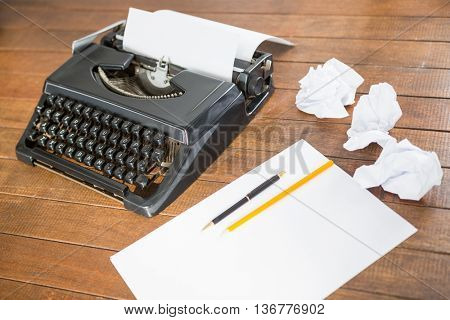 Picture of a type writer with paper and pen
