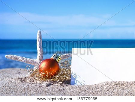 Blank white card with christmas decoration and sea shell on a tropical beach. Christmas holidays. Greeting card with copy space on the beach.