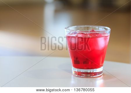 Red sweet drink in a glass on table