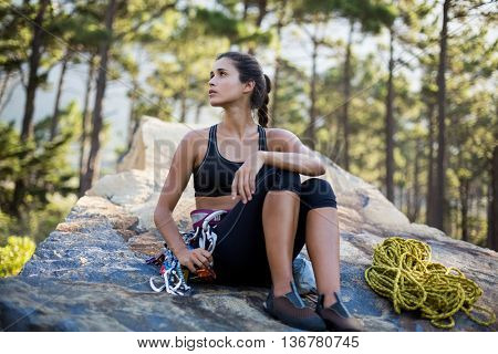 Woman sitting and posing with climbing equipment on the wood