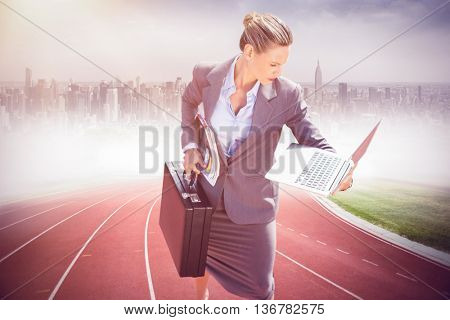 Businesswoman looking at her laptop against composite image of racetrack in city