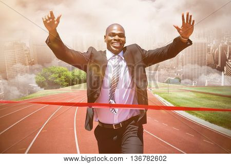 Businessman crossing the finish line against composite image of racetrack in city