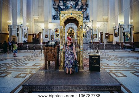 Tbilisi Georgia - July 18 2015. Woman prays in Holy Trinity Cathedral main cathedral of the Georgian Orthodox Church in Georgia