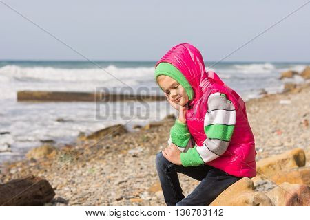 Girl Sitting On The Rocky Beach And The Sea Happily Lost In Thought Looking Down