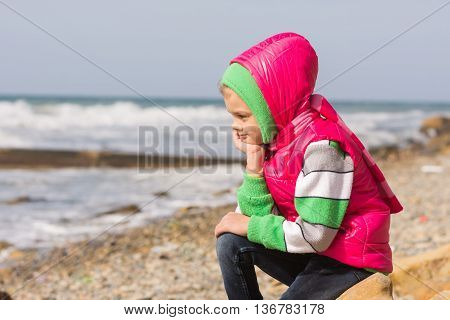 Girl Sitting On The Rocky Beach And The Sea Head On His Hand Looking To The Frame