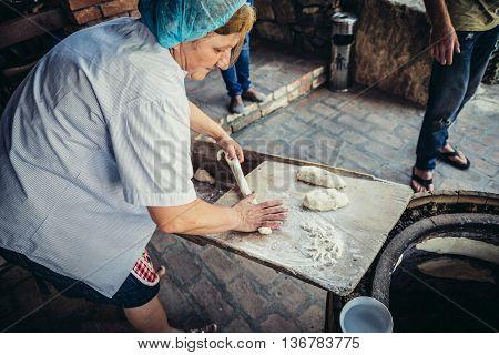 Napareuli Georgia - July 19 2015. Woman makes Georgian bread in Napareuli village