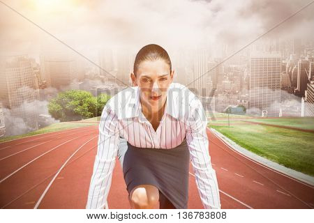 Businesswoman in starting blocks against composite image of racetrack in city