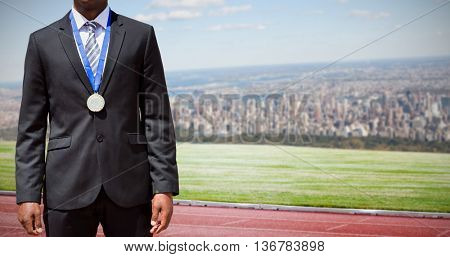 Businessman with medal against composite image of racetrack in city